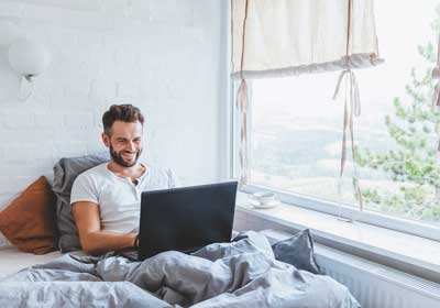 Man with laptop lounging on bed in apartment